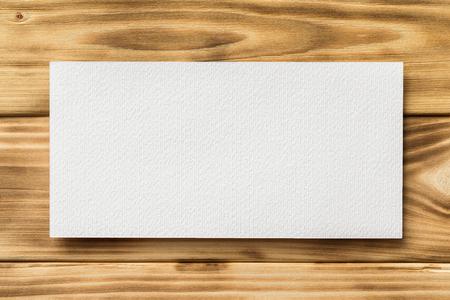 Макет горизонтальной белой лист бумаги на текстурированном фоне деревянного стола.