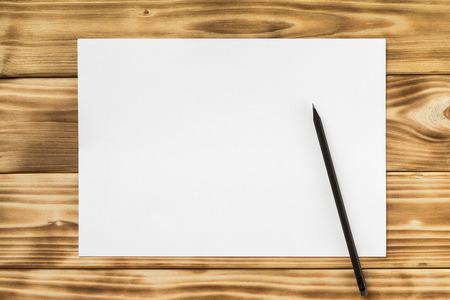 Макет из белого листа бумаги a4 и карандаш на фоне текстурированных деревянных столов.