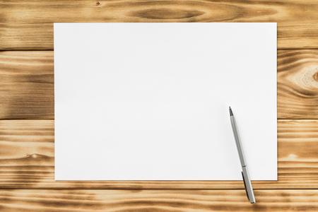 Макет из белого листа бумаги a4 и ручка на фоне текстурированного деревянного стола.