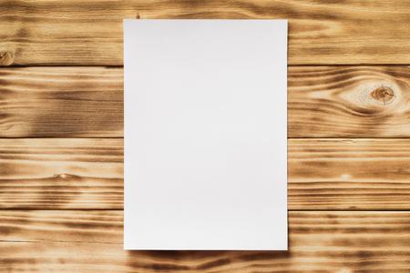 Mockup de la liste de papier blanc blanc a4 au fond de table en bois texturé. Banque d'images