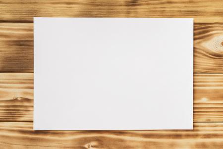 Макет горизонтального белого листа бумаги a4 на текстурированном деревянном столе. Фото со стока