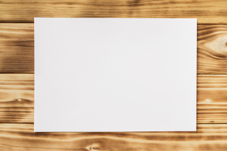 Mockup of horizontal white a4 paper list at textured wooden table background.