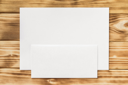 Макет пустой лист бумаги A4 и конверт на фоне деревянной доски. Фото со стока