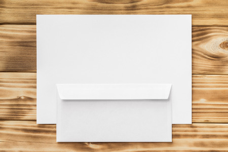 Mockup of blank A4 paper list and back side envelope at wooden board background.