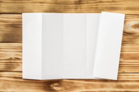 Макет белый открыл четыре раза брошюры и закрытых флаер, изолированных на фоне деревянных текстурированных борту