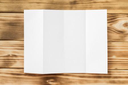 Макет белый открыл четыре раза брошюры, изолированных на деревянной текстурированной фоне