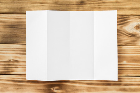 Mockup of white opened four fold brochure isolated at wooden textured board background