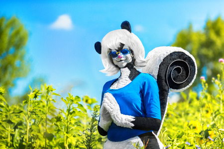 Portrait of female dressed in skunk comics costume outdoors at summer park background.