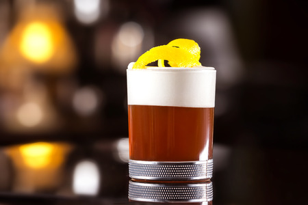Closeup image of glass of cocktail decorated with cream and lemon at bar stand background. Фото со стока