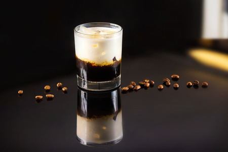 Closeup image of glass of black Russian cocktail and coffee beans at dark bar stand background.