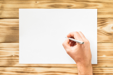 Mockup of male hand with pen writing at blank white paper list at wooden board background. Фото со стока