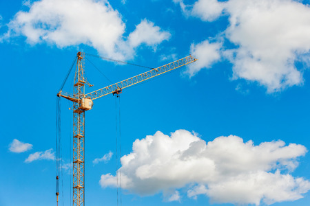 Closeup image of yellow crane lifting cargo outdoors at blue sly with clouds background.
