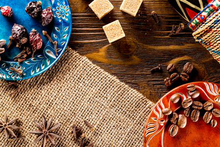 Colorful set of plates wiith spice, herb, coffee beans and sugar at wooden board background as natural wallpaper.