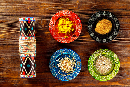 Closeup image of colorful ethnic style plates with spices and maraca at wooden table background.