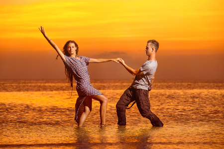 Sexy young couple is dancing at golden tropical sea sunset background.
