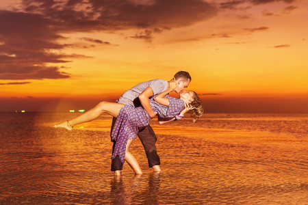 Young romantic couple is kissing standing at tropical sea background.