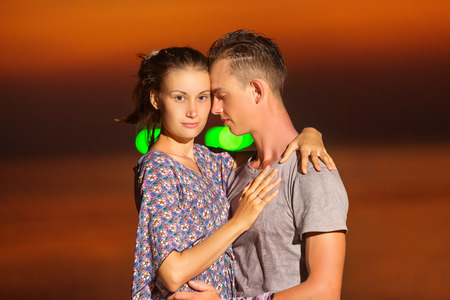Portrait of young romantic couple hugging at sea sunset background.