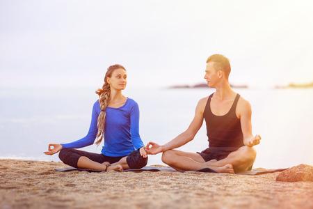 Couple is practising yoga meditatin pose at tropical sunrise sea background. Фото со стока