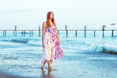 Lonely woman is walking along seashore background. Banque d'images