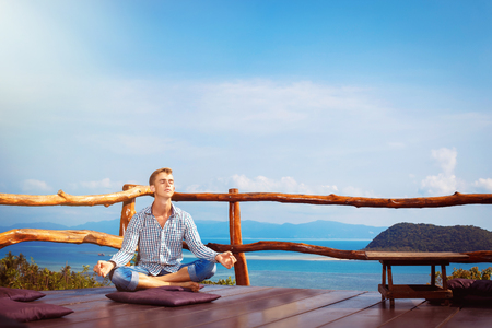 Happy man is sitting with closed eyes in yoga pose at wooden floor at summer tropical sea background.