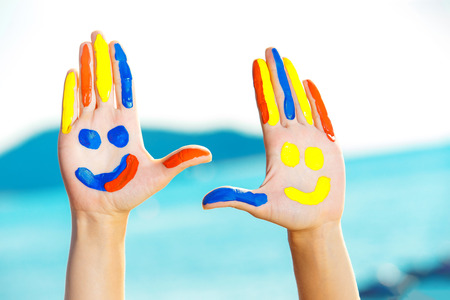 Closeup image of hands with colorful paint at blue summer outdoors background. Concept of happiness. Фото со стока