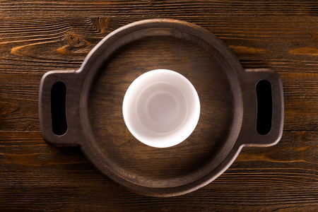 Mockup of empty white plate at wodden round tray at table background. Top view Фото со стока