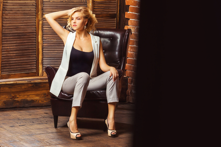 Portrait of modern business woman sitting in armchair at studio background.