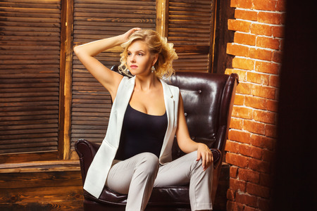 Closeup portrait of modern business woman sitting in armchair at studio background. Фото со стока