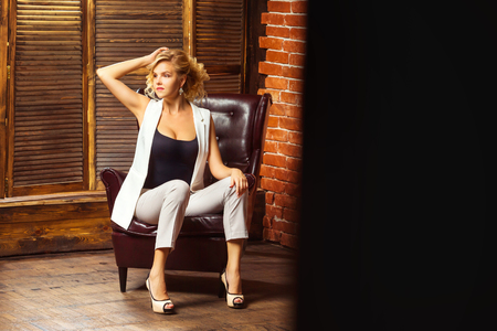 Portrait of modern sexy lady sitting in armchair at studio background.