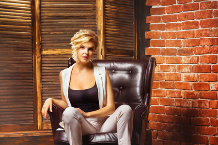 Closeup portrait of beautiful business style blonde woman sitting in armchair indoors.