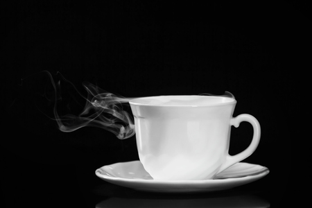 White cup of tea on saucer with smoke isolated at black background.  Banque d'images