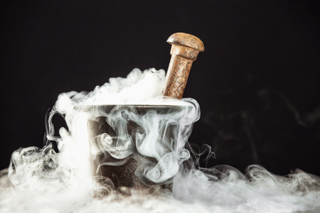 Closeup rusty vintage mortar filled with magic potion and deep smoke around at black background.