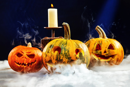 Halloween wallpaper with three jack-o-lantern pumpkins surrounded by smoke at blue background.
