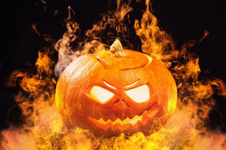 Closeup jack-o-lantern Halloween pumpkin with fire burning around at dark background. Foto de archivo