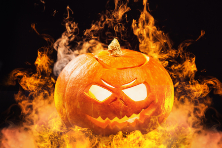 Ph�ng to h�nh jack-o-lantern Halloween pumpkin v?i l?a ch�y xung quanh ? n?n t?i. Kho ảnh