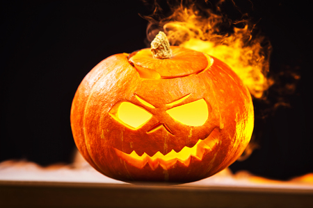 Closeup jack-o-lantern Halloween pumpkin with fire burning around at dark background. Banque d'images