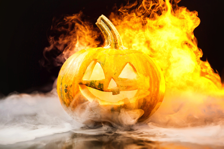 Closeup jack-o-lantern Halloween pumpkin with fire burning around at dark background. Фото со стока