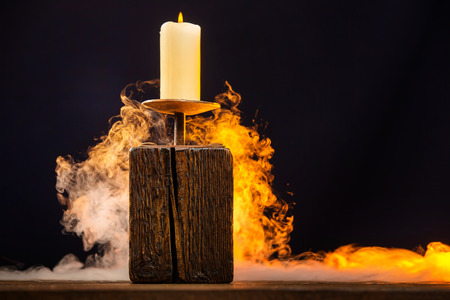 Closeup vintage wooden candlestick with candle surrounded by smoke at dark background. Banque d'images
