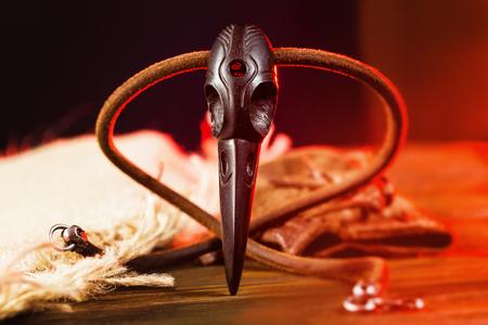 Closeup cráneo de cuervo de madera como un amuleto mágico de brujería en el fondo de luz roja.