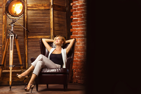 Closeup portrait of modern business woman sitting in armchair at studio background. Banque d'images