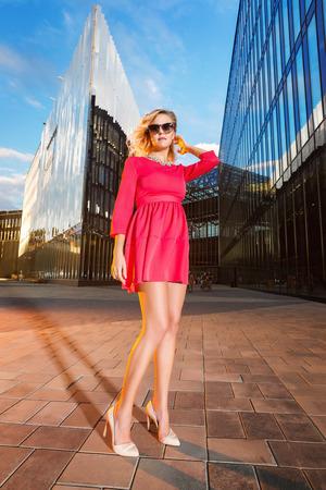 Hermosa mujer en vestido rosa está de pie en vidrio scyscrappers ciudad calle puesta de sol de fondo.