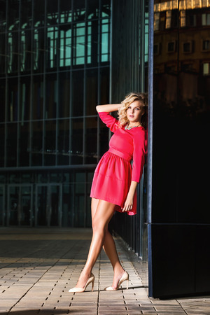 Joven y bella mujer en vestido de color rosa está de pie al aire libre en la noche de la calle urbana cerca de fondo de pared de vidrio. Foto de archivo