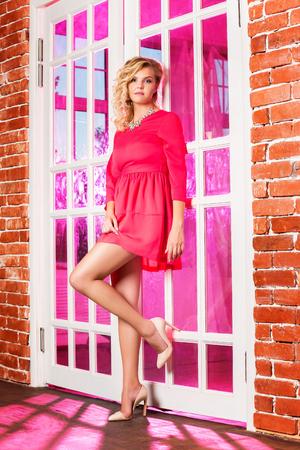 Retrato de la mujer rubia joven atractiva en vestido rosado cerca de una puerta con el fondo ligero púrpura. Foto de archivo