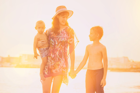 Vintage style portrait of happy family of mom and two brothers at sea sunset background.