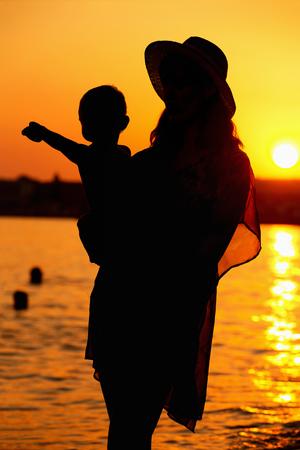 Silueta de la madre y el hijo al aire libre en el fondo del atardecer naranja mar.