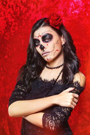 Closeup halloween estilo retrato de mujer hermosa con arte facial - cráneo mexicano tradicional en fondo rojo.
