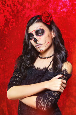 Closeup halloween style portrait of beautiful woman with facial art - traditional mexican skull at red background. Stock Photo