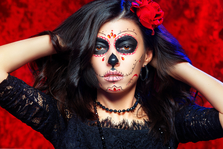 Closeup halloween style portrait of beautiful woman with facial art - traditional mexican skull at red background. Kho ảnh