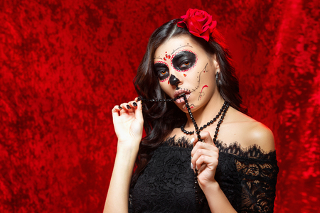 Closeup halloween style portrait of beautiful woman with facial art - traditional mexican skull beads with teeth at red background.