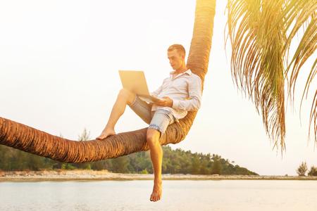 El hombre moderno joven está sentándose en la palmera y el trabajo con la computadora portátil en el fondo tropical.